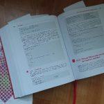 aufgeschlagenes Buch mit Zettelmarkierungen