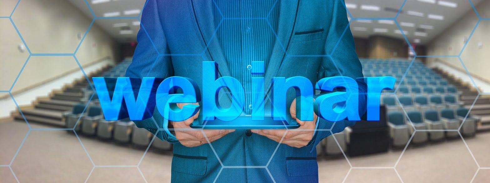 Mann mit Tablet in der Hand vor leerem Hörsaal, Schriftzug Webinar